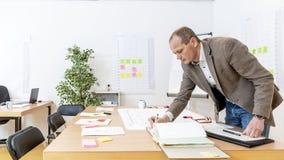 Руководитель производства подписывая на пересматриванных чертежах дизайна продукции стоковые фото