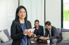 Руководитель коммерсантки используя таблетку с командой в корпоративной встрече Стоковые Фотографии RF