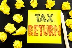 Рукописный текст показывая налоговую декларацию Сочинительство концепции дела для учитывая возвращения денег написанного на липко стоковое изображение