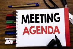 Рукописный текст показывая повестку дня заседания Концепция дела для плана план-графика дела написанного на тетради, деревянной п Стоковые Изображения