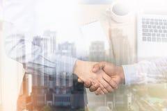 Рукопожатие бизнесмена на предпосылке стола города и офиса Стоковые Изображения RF