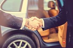 Рукопожатие бизнесменов над предпосылкой автомобиля Стоковое Фото
