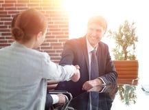 Рукопожатие бизнесменов на столе стоковая фотография