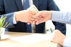 Рукопожатие бизнесменов с деньгами breton стоковое фото
