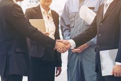 Рукопожатие бизнесменов с предпосылкой команды дела Стоковые Фото