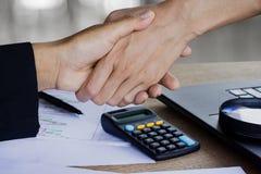 Рукопожатие 2 бизнес-леди после работать совместно и приходить их проект на офисе с некоторой финансовой бумажной диаграммой стоковая фотография