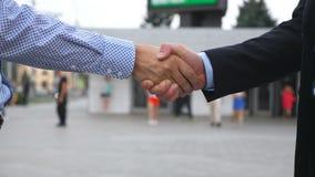 Рукопожатие дела с запачканной предпосылкой города 2 бизнесмена приветствуя один другого в городской среде Трясти  Стоковые Фото