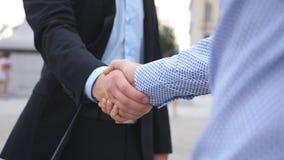 Рукопожатие дела с запачканной предпосылкой города 2 бизнесмена приветствуя один другого в городской среде Трясти  Стоковое фото RF