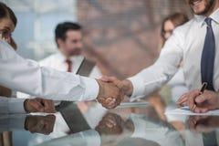 Рукопожатие деловых партнеров на предпосылке deskto Стоковое Изображение