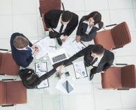 рукопожатие деловых партнеров перед беседами около настольного компьютера внутри Стоковые Изображения RF