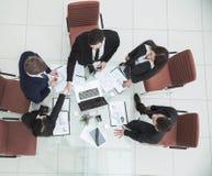 рукопожатие деловых партнеров перед беседами около настольного компьютера внутри Стоковое фото RF