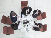 рукопожатие деловых партнеров перед беседами около настольного компьютера внутри Стоковые Изображения