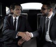 Рукопожатие деловых партнеров сидя в автомобиле Стоковая Фотография RF