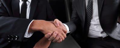 Рукопожатие деловых партнеров сидя в автомобиле Стоковые Фото