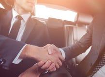Рукопожатие деловых партнеров сидя в автомобиле Стоковое Изображение