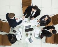 рукопожатие деловых партнеров перед беседами около настольного компьютера внутри Стоковое Изображение
