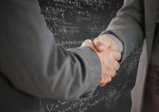 Рукопожатие против серой стены с doodles математики Стоковые Фотографии RF