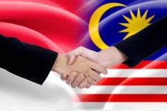 Рукопожатие людей с флагами индонезийца и малайзийца Стоковое Изображение