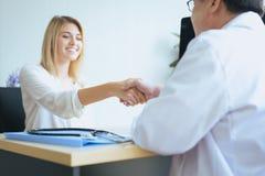 Рукопожатия женщины пациента и человека доктора успокаивать консультация и поощрение в палате, конце вверх стоковые фото