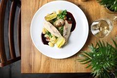 Рулады цыпленка заполненные с горгонзолой, который служат с лук-пореем зажаренным в масле, варениках, зеленых горохах и соусе вин стоковые изображения