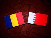 Румынский флаг с бахрейнским флагом на пне дерева Стоковое Изображение