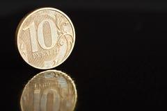 Русская монетка 10 рублевок на крае на черной предпосылке с отражением с космосом экземпляра Стоковая Фотография RF