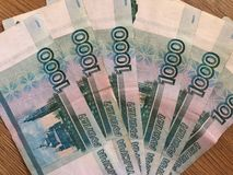 Русские банкноты в деноминациях 1000 рублей на деревянной предпосылке стоковые фотографии rf
