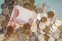 Русские банкноты и монетки денег на зеленой предпосылке Стоковое Изображение