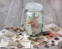 Русские бумажные деньги и металл в стеклянном опарнике Стоковая Фотография