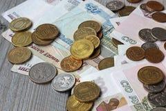 Русские бумажные деньги и металл на таблице Стоковая Фотография