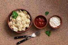 Русские вареники мяса pelmeni еды со сметаной и кетчуп аранжированными в ряд на коричневой каменной предпосылке Надземный взгляд, стоковое фото rf
