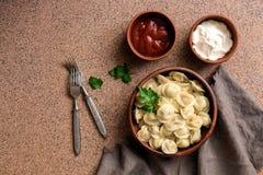 Русские вареники мяса pelmeni еды со сметаной и томатным соусом на коричневой каменной столешнице Взгляд сверху, плоское положени стоковые фото