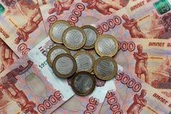 Русские деньги 5 деноминаций тысяч и коммеморативные монетки лежат на смешанной таблице Стоковые Фотографии RF