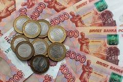 Русские деньги 5 деноминаций тысяч и коммеморативные монетки лежат на смешанной таблице Стоковое Изображение