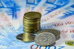 Русские кредитки и монетки Пригорошня монеток на новых русских банкнотах в деноминациях 2000 и 200 рублей стоковое фото