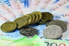 Русские кредитки и монетки Пригорошня монеток на новых русских банкнотах в деноминациях 2000 и 200 рублей стоковые изображения