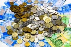 Русские кредитки и монетки Пригорошня монеток на новых русских банкнотах в деноминациях 2000 и 200 рублей стоковая фотография rf