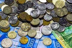 Русские кредитки и монетки Пригорошня монеток на новых русских банкнотах в деноминациях 2000 и 200 рублей стоковая фотография