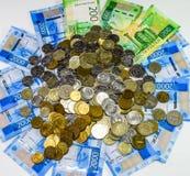 Русские кредитки и монетки Пригорошня монеток на новых русских банкнотах в деноминациях 2000 и 200 рублей стоковые изображения rf