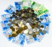 Русские кредитки и монетки Пригорошня монеток на новых русских банкнотах в деноминациях 2000 и 200 рублей стоковое изображение