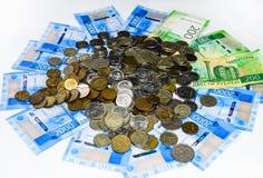 Русские кредитки и монетки Пригорошня монеток на новых русских банкнотах в деноминациях 2000 и 200 рублей стоковое изображение rf