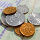 Русские монетки металла на фоне банковской книжки на предъявителя Стоковая Фотография