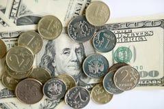 Русские рубли монеток на банкнотах долларов Стоковая Фотография
