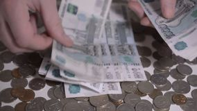 Русские щебни и монетки денег над белыми руками таблицы подсчитывают отснятый видеоматериал hd замедленного движения денег сток-видео