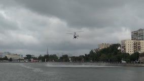 Русский вертолет министерства аварийных ситуаций комплектует вверх воду для того чтобы потушить огонь сток-видео
