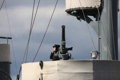 Русский матрос военно-морского флота около старого оружия ` s корабля на предпосылке облачного неба Стоковое Изображение RF