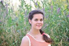 Русский подросток девушки в предпосылке wildflowers Стоковые Фотографии RF