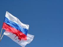 Русский флаг на поляке против голубого неба Стоковое Изображение RF