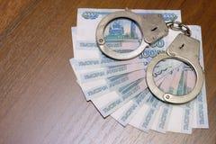 10 русских счетов тысячи рублей с наручниками лежат на коричневой таблице Концепция нарушения закона в Стоковая Фотография
