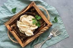 Русское vareniki еды с картошками послужено в шаре на деревянной коробке Серая предпосылка, плоское положение стоковые изображения rf